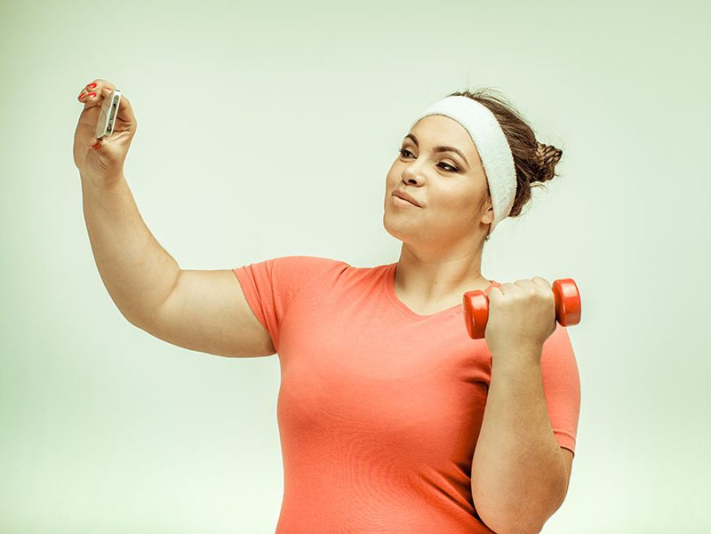 Overweight woman taking selfie