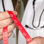 weight loss doctor with measuring tape